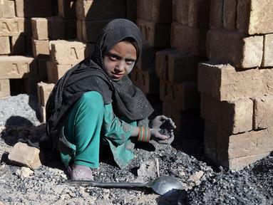 Seorang anak mengumpulkan sisa batu bara yang digunakan di pabrik batu bata di pinggiran Kabul, Afghanistan, Rabu (12/6/2019). Ribuan anak Afghanistan bekerja mencari uang untuk menghidupi keluarga mereka. (AP Photo/Rahmat Gul)