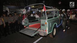 Petugas mengatur parkir mobil Land Rover klasik bak terbuka tumpangan Jokowi-Ma`ruf di gedung KPU Pusat, Jakarta, Jumat (21/9). Jokowi-Ma`ruf ke KPU untuk mengambil nomor urut Pilpres pasangan Capres dan Wapres 2019- 2024. (Liputan6.com/Fery Pradolo)