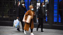 Orang-orang berjalan dengan mengenakan masker saat mereka membawa tas belanja di Regent Street setelah pelonggaran pembatasan virus corona COVID-19 menyusul berakhirnya kebijakan penguncian nasional atau lockdown kedua di Inggris, di London, Sabtu (5/12/2020). (AP Photo/Alberto Pezzali)