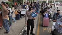 Polisi mengingatkan jaga jarak saat calon penumpang mengntre untuk rapid test antigen di Terminal 2 Bandara Soekarno-Hatta, Tangerang, Banten, Selasa (22/12/2020). Layanan rapid test antigen dibanderol dengan harga Rp 200 ribu. (merdeka.com/Arie Basuki)