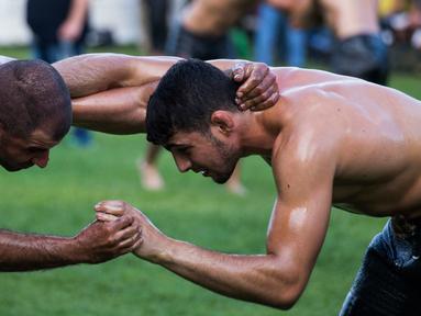 Dua pegulat sedang beraksi berusaha saling menjatuhkan dalam kompetisi tahunan gulat minyak tradisional di Sochos, Yunani, 30 Juni 2018. Lebih dari seratus drum minyak zaitun habis untuk melumuri sekujur tubuh setiap peserta. (AP/Giannis Papanikos)