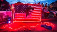 Bendera Amerika dengan wajah Elvis Presley terpajang di depan bekas rumah Elvis di Graceland, Memphis, Tennessee, Selasa (15/8). Para penggemar menghadiri peringatan 40 tahun kematian bintang rock n roll tersebut. (AP Photo/Brandon Dill)