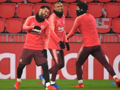 Lionel Messi dan Arturo Vidal tampak menikmati saat latihan berlangsung jelang digelarnya laga lanjutan Grup B Liga Champions kontra PSV Eindhoven, Rabu (28/11). Dalam laga kali ini Luis Suarez diragukan tampil karena cedera. (AFP/Emmanuel Dunand)