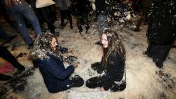 Dua orang wanita tertimbun kapas saat mengikuti flash mob perang bantal selama empat menit di Old Town Square di Praha,Ceko (22/12). flash mob perang bantal ini dilakukan jelang pergantian akhir tahun. (REUTERS/ David W Cerny)