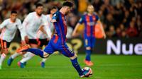 Striker Barcelona Lionel Messi mengeksekusi penalti ke gawang Valencia pada laga La Liga di Stadion Camp Nou, Barcelona, Minggu (19/3/2017). (AFP/Lluis Gene)