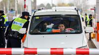 Polisi menggunakan termometer digital untuk mengukur suhu pengemudi mobil di sebuah pos pemeriksaan gerbang tol di Wuhan, Provinsi Hubei, China, Kamis (23/1/2020). Pemerintah China mengisolasi Kota Wuhan yang berpenduduk sekitar 11 juta jiwa untuk menahan penyebaran virus corona. (Chinatopix via AP)