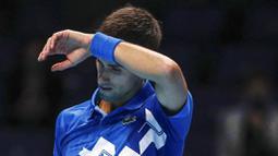 Petenis Serbia, Novak Djokovic, mengusap keringat saat melawan Petenis Rusia, Daniil Medvedev, pada ATP Finals di O2 Arena, London, Kamis (19/11/2020). Petenis nomor satu dunia itu takluk 3-6 3-6. (AP/Frank Augstein)