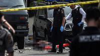 Polisi memeriksa jenazah seorang yang diduga sebagai pelaku bom bunuh diri di Mapolrestabes Medan, Sumatera Utara, Rabu (13/11/2019). Pelaku bom bunuh diri mengunakan atribut ojek online dan meledakkan diri di sekitar kantin Mapolrestabes Medan. (ALBERT