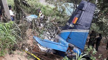 Petugas penyelamat memeriksa puing-puing  pesawat milik Angkatan Udara Sri Lanka yang jatuh di daerah pegunungan penghasil teh di Haputale, Jumat (3/1/2020). Empat orang kru yang berada di pesawat tewas dalam insiden tersebut. (Photo by STR / AFP)