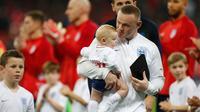 Striker Inggris, Wayne Rooney meggendong anaknya sebelum pertandingan persahabatan melawan Amerika Serikat (AS) di Stadion Wembley, Inggris (16/11). Wayne Rooney merupakan pencetak gol terbanyak di Timnas Inggris. (AFP Photo/Ian Kington)