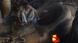 Seorang pedagang Pakistan megaduk kacang pinus  saat dipanggang di pasar di Lahore (13.12). Pakistan merupakan salah satu penghasil kacang pinus terbaik di dunia. (AFP Photo/Arif Ali)