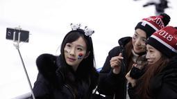 Tiga wanita fans Korea Selatan berselfie sebelum pertandingan babak penyisihan hoki wanita antara Swedia dan gabungan Korea di Olimpiade Musim Dingin 2018 di Gangneung, Korea Selatan, (12/2). (AP Photo / Julio Cortez)
