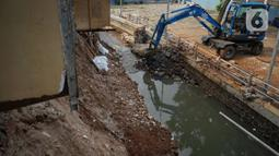 Alat berat mengeruk beton turap saluran air yang longsor di kawasan Jagakarsa, Jakarta, Kamis (17/9/2020). Selain karena hujan lebat, longsor diduga karena erosi tanah akibat pembuangan saluran air pencuci piring dan toilet dari warung makan di sekitar bantaran. (Liputan6.com/Immanuel Antonius)