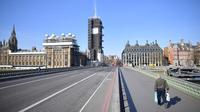 Sebuah gambar menunjukkan Gedung Parlemen (kiri) di ujung Westminster Bridge yang kosong dengan seorang pejalan kaki di trotoar London setelah pemerintah Inggris setempat memberlakukan lockdown akibat pandemi Covid-19 pada 24 Maret 2020. (Photo by JUSTIN TALLIS / AFP)