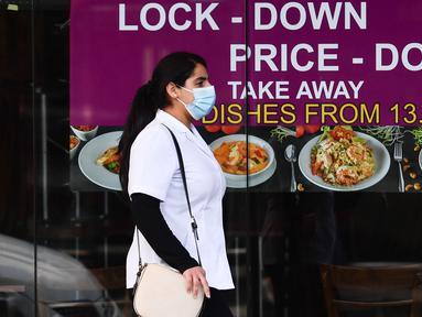 Seorang wanita yang mengenakan masker berjalan melewati sebuah restoran di Melbourne, Negara Bagian Victoria, Australia, 31 Agustus 2020. Kasus baru COVID-19 di Victoria turun setelah sebulan memberlakukan karantina wilayah (lockdown) Tahap 4 di ibu kotanya, Melbourne. (Xinhua/Bai Xue)