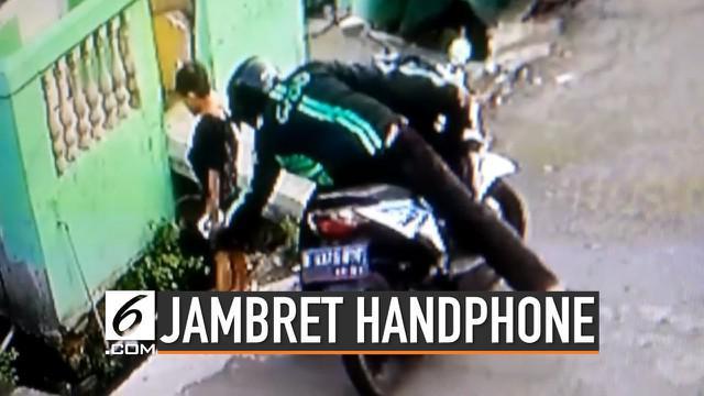 Seorang pengemudi ojek online terekam cctv saat menjambret handphone seorang bocah. Polisi telah mengetahui identitas pelaku dan kini sedang melakukan pengejaran.