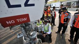 Menteri Perhubungan (Menhub) Budi Karya Sumadi mengecek roda pesawat saat meninjau pelayanan arus mudik di Bandara Halim Perdanakusuma, Jakarta, Senin (11/6). (Merdeka.com/Iqbal Nugroho)