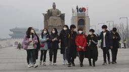 Para siswa mengenakan masker berjalan di Gwanghwamun Plaza di Seoul, Korea Selatan (10/12/2019). Kementerian Lingkungan Hidup Korsel menegakkan serangkaian tindakan darurat untuk mengurangi polusi debu halus, termasuk melarang kendaraan tertentu dari jalan pusat kota. (AP Photo/Ahn Young-joon)