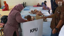 Panitia Pemungutan Suara (PPS) mendampingi lansia penghuni Panti Jompo Tresna Werdha Budi Mulia 1 yang menggunakan hak pilihnya dalam Pemilu 2019 di Cipayung, Jakarta Timur, Rabu (17/4). Pendampingan dilakukan terhadap lansia yang sedang sakit. (Liputan6.com/Immanuel Antonius)