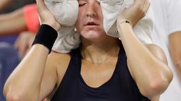 Petenis Republik Ceko, Karolina Muchova menaruh handuk es di kepalanya karena kepanasan saat istirahat bertanding melawan Garbine Muguruza asal Spanyol di putaran kedua AS Terbuka, New York, Kamis (30/8).  (AP Photo/Jason DeCrow)