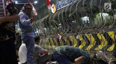 Peserta aksi massa Gerakan Nasional Kedaulatan Rakyat melakukan salat maghrib saat unjuk rasa di depan Gedung Bawaslu, Jalan MH Thamrin, Jakarta, Selasa (21/5/2019). Dalam aksinya, mereka Bawaslu memeriksa hasil Pemilu 2019 yang dinilai banyak terdapat kecurangan. (Liputan6.com/Helmi Fithriansyah)
