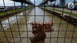 Seorang anak bermain dan berenang di aliran Kalimalang, Jakarta, Sabtu (15/2/2020). Cuaca yang tidak menentu membuat aliran air terkadang menjadi deras sehingga akan membahayakan keselamatan anak-anak saat bermain dan berenang. (merdeka.com/Imam Buhori)