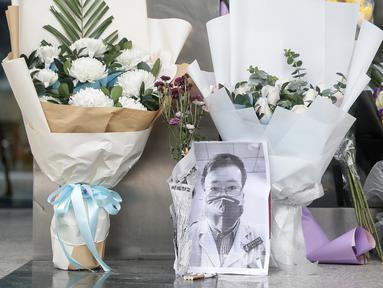 Karangan bunga dan foto mendiang dokter Li Wenliang terlihat di Cabang Houhu Rumah Sakit Pusat Wuhan di Wuhan di provinsi Hubei, China, Jumat, (7/2/2020). Li Wenliang sebelumnya memberikan peringatan kepada publik tentang potensi munculnya virus corona pada Desember 2019. (AFP/STR)