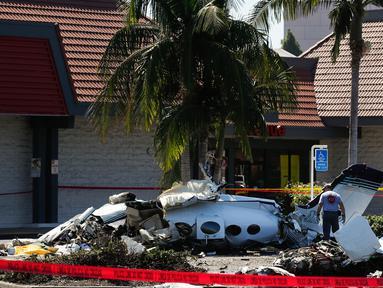 Tim investigasi menyelidiki reruntuhan sebuah pesawat kecil yang jatuh ke area parkir pusat perbelanjaan di Santa Ana, California, Senin (6/8). Dalam insiden itu, sebanyak lima orang penumpang pesawat meninggal dunia. (AP/Jae C. Hong)