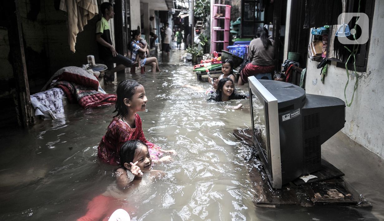 Anak-anak bermain air saat banjir merendam permukiman warga di Kemang Timur XI, Jakarta Selatan, Minggu (21/2/2021). Longsor yang merusak rumah dan menutup aliran kali membuat RT 10 dan 12, RW 03, Kelurahan Bangka, Kecamatan Mampang Prapatan masih terendam banjir. (merdeka.com/Iqbal S. Nugroho)