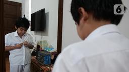 Siswa SD Islam Al Azhar 4 Muhammad Risyad (10) memakai seragam saat akan mengikuti kegiatan belajar mengajar secara daring dari kediamannya, Bintaro, Jakarta, Senin (13/7/2020). Memasuki tahun ajaran baru, kegiatan belajar mengajar diawali dengan perkenalan para siswa. (Liputan6.com/Herman Zakharia)