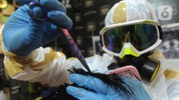 Seorang tukang cukur mengenakan alat pelindung diri (APD) saat memangkas rambut pelanggannya di Chemot Barbershop, Ciawi, Bogor, Jawa Barat, Minggu (5/4/2020). Penggunaan APD buatan sendiri tersebut merupakan sosialisasi kepada pelanggan. (merdeka.com/Arie Basuki)