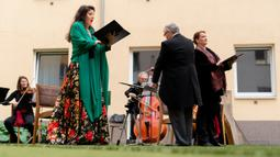 "Penyanyi Monika Medek dan Dagmar Dekanovsky serta orkestra Camerata Carnutum menggelar konser jendela (Fensterkonzert) di halaman Zeitgeist Hotel di Wina, Sabtu (30/5/2020). ""Konser jendela"" diadakan untuk merayakan pembukaan kembali hotel di Austria di tengah pandemi COVID-19. (JOE KLAMAR/AFP)"