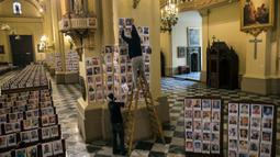 Pekerja menempelkan potret korban meninggal akibat virus corona di dalam Katedral, di Lima, Peru pada 13 Juni 2020. Misa Minggu di Katedral Lima dihadiri lebih dari 4.000 potret mereka yang telah meninggal dalam pandemi Covid-19 yang menyebar di Peru. (AP Photo/Rodrigo Abd)