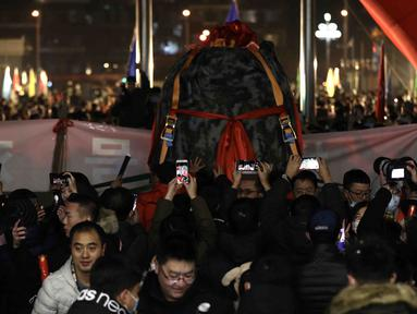 Orang-orang merayakan kedatangan kapsul pembawa pulang (return capsule) wahana antariksa China, Chang'e-5, di Akademi Teknologi Luar Angkasa China di Beijing, ibu kota China (17/12/2020). Kapsul tersebut diterbangkan ke Beijing pada Kamis (17/12) malam waktu setempat. (Xinhua/Jin Liwang)