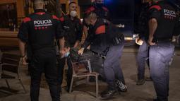 Seorang pemuda ditahan oleh Mossos d'Escuadra, kepolisian regional Catalonia, setelah jam malam di Barcelona pada 1 November 2020. Pemerintah Spanyol menetapkan pembatasan gerak atau jam malam yang berlaku pukul 22.00 untuk mengendalikan lonjakan kasus Covid-19. (AP Photo/Emilio Morenatti)