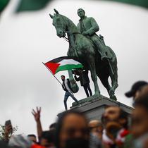 Seorang pria mengibarkan bendera Palestina sambil meneriakkan slogan-slogan dengan orang lain selama protes untuk mendukung warga Palestina di Jalur Gaza di Brussel, Belgia, Sabtu (15/5/2021). (AP Photo/Francisco Seco)
