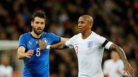 Pemain timnas Italia, Antonio Candreva berebut bola dengan pemain timnas Inggris, Ashley Young dalam laga persahabatan di Stadion Wembley, Rabu (28/3).  Sempat tertinggal, Italia menahan imbang Inggris 1-1. (AP Photo/Alastair Grant)