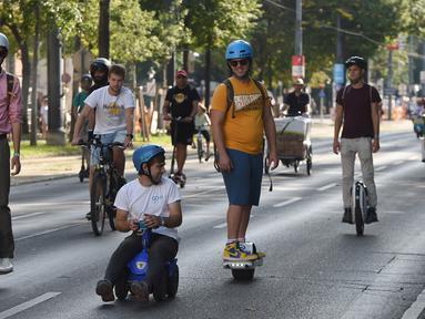 """Sejumlah orang mengikuti parade kendaraan listrik di Wina, Austria, 13 September 2020. Ratusan kendaraan listrik ambil bagian dalam parade E-Mobility """"Rock the Ring"""" untuk mempromosikan mobilitas bebas emisi dan ramah iklim. (Xinhua/Guo Chen)"""