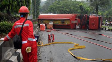Petugas pemadam api dari Pertamina melihat kondisi truk tangki BBM yang terbalik di ruas Jalan Tegar Beriman Kabupaten Bogor, Jumat (15/4/2016). Menurut warga, truk tangki terbalik sekitar pukul 05.00 dini hari. (Liputan6.com/Helmi Fithriansyah)