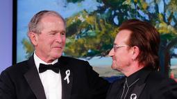 Presiden AS ke-43 George W. Bush berjabat tangan vokalis U2 Bono selama gala untuk Forum Kepemimpinan di Institut George W. Bush di Dallas, AS (19/4). Dalam acara ini Bush mempersembahkan Bono medali Distinguished Citizenship. (AP Photo/Brandon Wade)