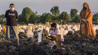 Keluarga berdoa untuk kerabat mereka di lokasi pemakaman korban virus corona COVID-19 di TPU Keputih, Surabaya, Jawa Timur, Sabtu (17/7/2021). Di Kota Surabaya terdapat dua tempat lahan pemakaman khusus blok COVID-19 yakni TPU Keputih dan TPU Babat Jerawat. (JUNI KRISWANTO/AFP)