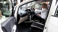 Seorang wanita menjajal mobil listrik hibah dari Mitsubishi Motors kepada Kementerian Perindustrian (Kemenperin) di Jakarta, Senin (26/2). Mobil listrik ini merupakan bagian dari studi bersama Mitsubishi Motors dengan Kemenperin. (Liputan6.com/JohanTallo)