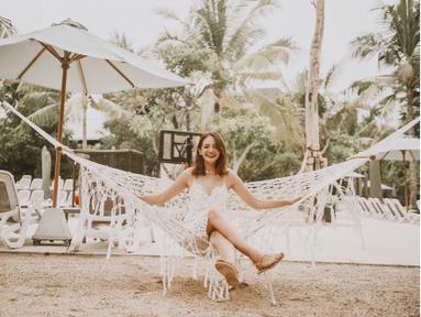 Enzy terlihat bahagia saat liburan ke Bali. Menggunakan pakaian berwarna putih, dengan dekorasi barang di sekitarnya yang serba putih, ia duduk dengan ceria di tempat tidur gantung jaring yang juga berwarna putih. (Liputan6.com/IG/@enzystoria)