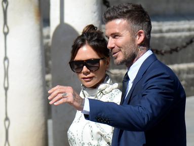 Mantan gelandang Real Madrid David Beckham dan istrinya Victoria Bekcham tiba di gereja menghadiri upacara pernikahan bek Sergio Ramos dan Pilar Rubio di Katedral Seville, Spanyol (15/6/2019). (AFP Photo/Cristina Quicler)