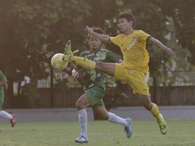 Striker Vamos Indonesia, Dony, berebut bola dengan pemain PS Tira Persikabo U-18 pada pertandingan persahabatan di Lapangan A GBK, Jakarta, Rabu (29/5). Kedua klub bermain imbang 1-1. (Bola.com/Yoppy Renato)