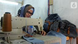 Perajin Risma Eljundi menyelesaikan pembuatan tas dari bahan celana jeans bekas di Legok, Tangerang, Banten, Senin (11/11/2019). Tas berbahan jeans dijual dengan harga Rp 150 ribu hingga Rp 250 ribu. (merdeka.com/Arie Basuki)