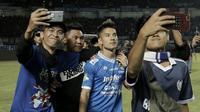 Suporter melakukan foto bersama dengan pemain Persib Bandung, Kim Jeffrey Kurniawan, usai mengalahkan Persija Jakarta pada laga Liga 1 di Stadion GBLA, Jawa Barat, Minggu (23/9/2018). Persib menang 3-2 atas Persija. (Bola.com/M Iqbal Ichsan)