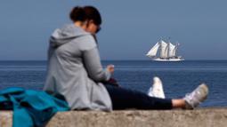 Seorang wanita beristirahat saat sebuah kapal berlayar di sepanjang pantai Laut Baltik dekat Gdynia, Polandia utara (24/5/2019). Perairan Laut Baltik mengalir ke Kattegat dan Laut Utara melewati Öresund, Sabuk Besar dan Sabuk Kecil. (AP Photo/Darko Vojinovic)