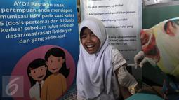 Ekspresi seorang anak saat mengikuti Bulan Imunisasi Anak sekolah (BIAS) di SDN 11 Pagi, Lubang Buaya, Jakarta, Selasa (4/10). Kegiatan ini untuk mewujudkan Indonesia bebas dari kanker serviks. (Liputan6.com/Faizal Fanani)
