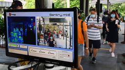 Pengunjung berjalan melalui area pemeriksaan suhu pada hari pertama pembukaan Kebun Binatang Singapura untuk umum di Singapura, Senin (6/7/2020). Kebun binatang yang hampir tiga bulan ditutup akibat pandemi virus corona ini dibuka kembali dengan penerapan protokol kesehatan. (Roslan RAHMAN/AFP)